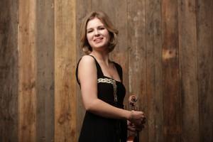 Cornelia Löscher vor einer Holzwand mit Violine